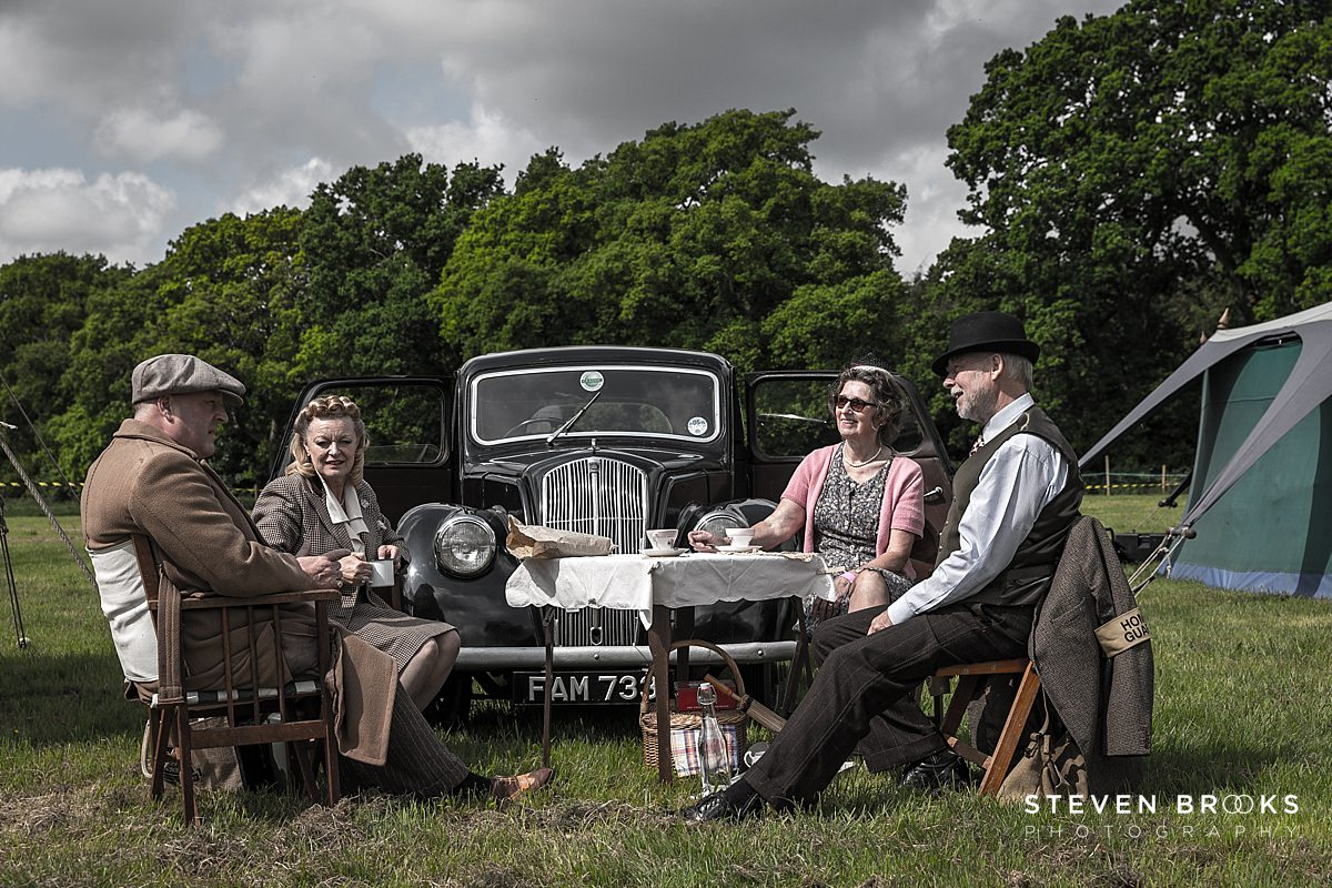 Norfolk photographer steven brooks photographs Britain Does Vintage at Stody Lodge two couples sitting around picnic table in vintage clothes