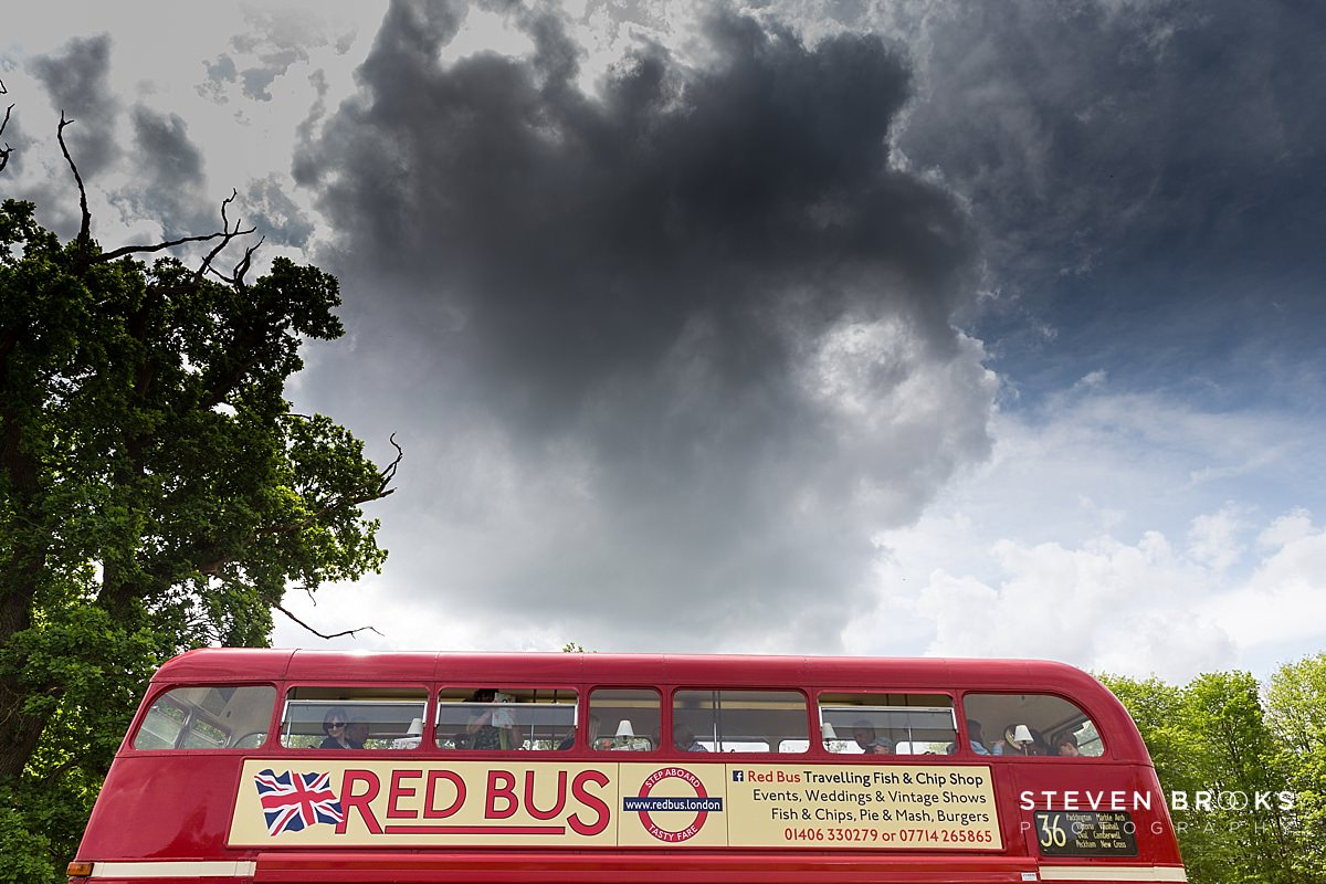 Norfolk photographer steven brooks photographs a red bus roof under dark clouds at Britain Does Vintage at Stody Lodge