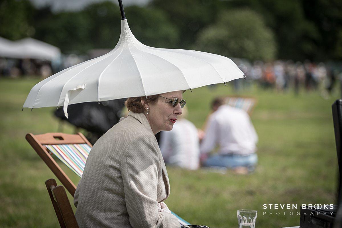 Norfolk photographer steven brooks photographs cwoman undr umbrella vintage clothes at Britain Does Vintage in Noirfolk