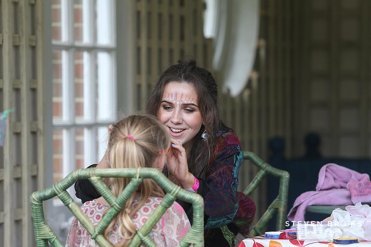 Norfolk photographer steven brooks photographs a young womans face painting a child at Britain Does Vintage in Norfolk
