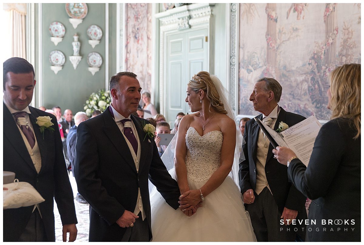 Leeds Castle wedding photographer steven brooks photographs the bride and groom in the wedding ceremony room looking back at guests