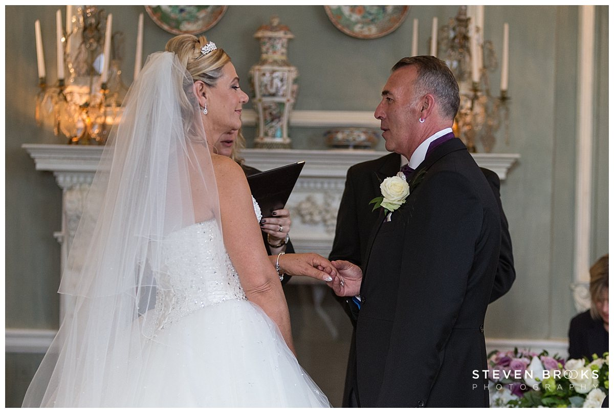Leeds Castle wedding photographer steven brooks photographs the bride and groom in the wedding ceremony room taking their vows