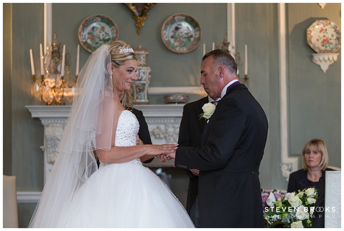 Leeds Castle wedding photographer steven brooks photographs the bride and groom in the wedding ceremony room at Leeds Castle exchanging rings