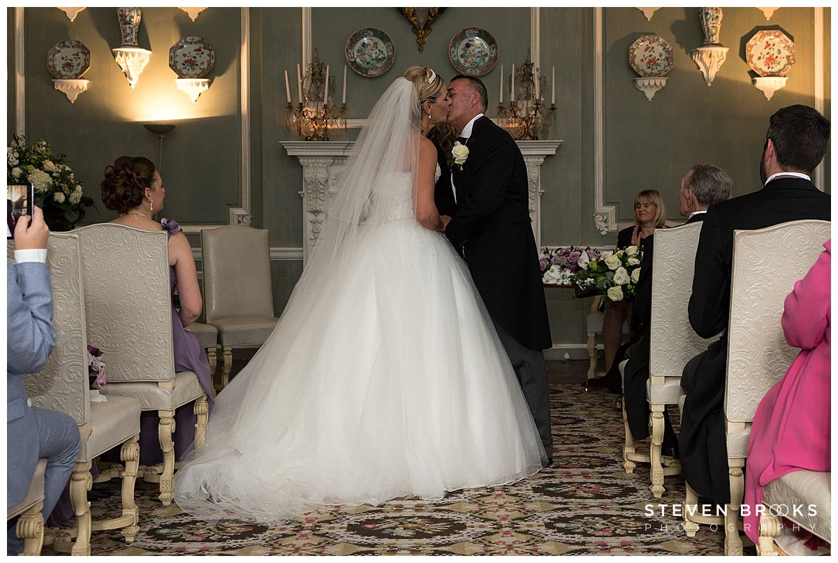 Leeds Castle wedding photographer steven brooks photographs the bride and groom in the wedding ceremony room at Leeds Castle and their first kiss