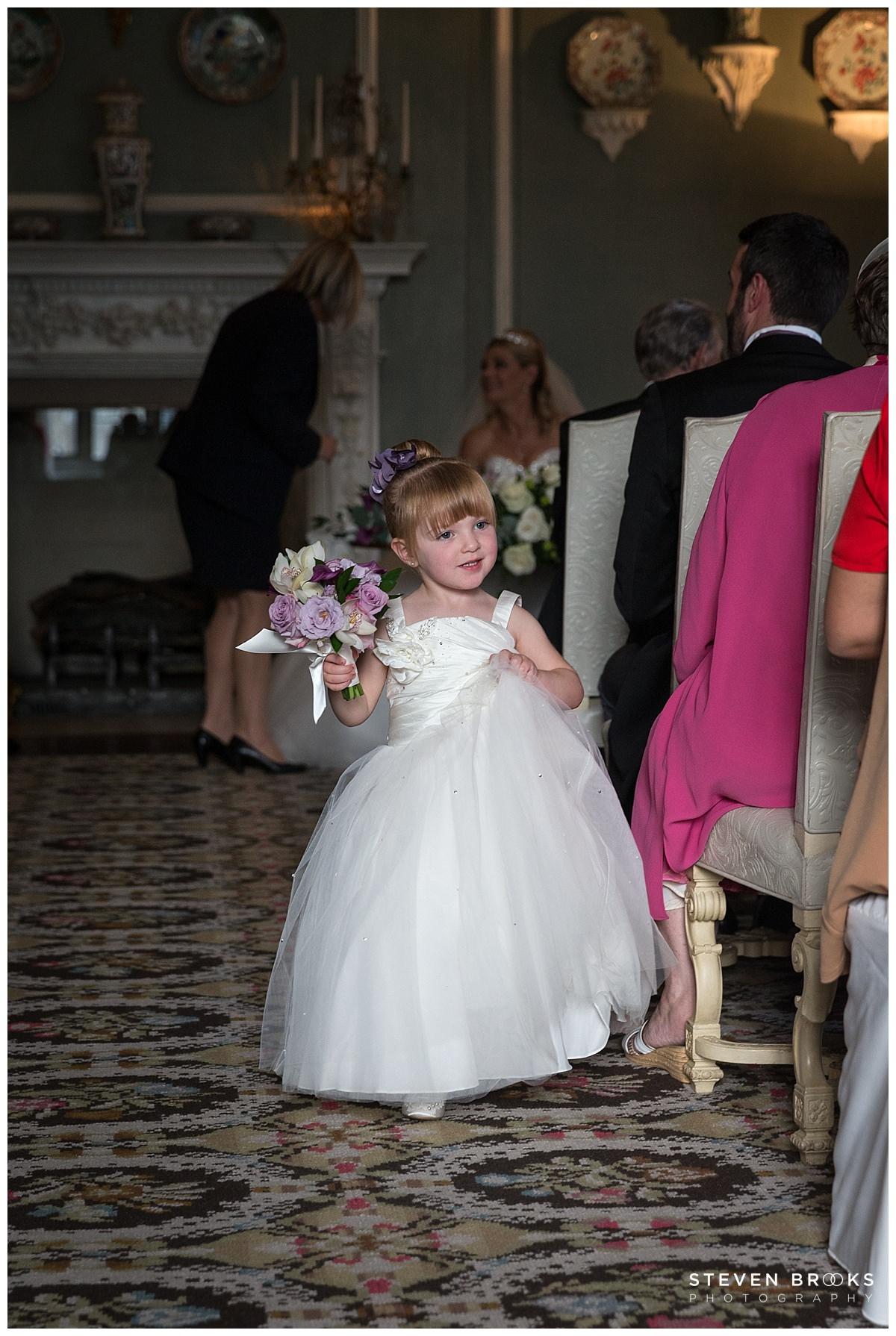 Leeds Castle wedding photographer steven brooks photographs a flower girl in the wedding ceremony room at Leeds Castle