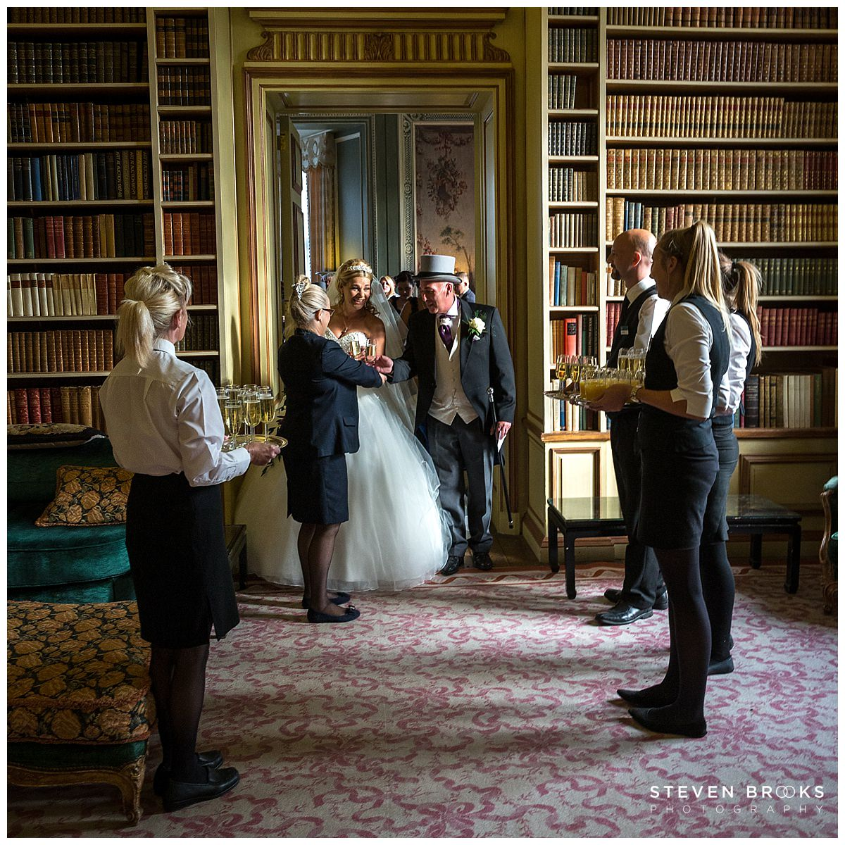 Leeds Castle wedding photographer steven brooks photographs the bride and groom in the Library at Leeds Castle to a welcome drink