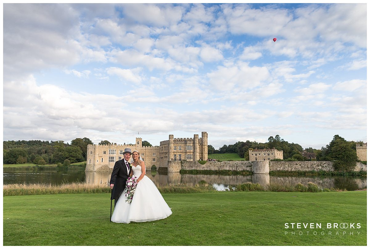 Leeds Castle wedding photographer steven brooks photographs the bride and groom in front of Leeds Castle with hot air balloon in the distance