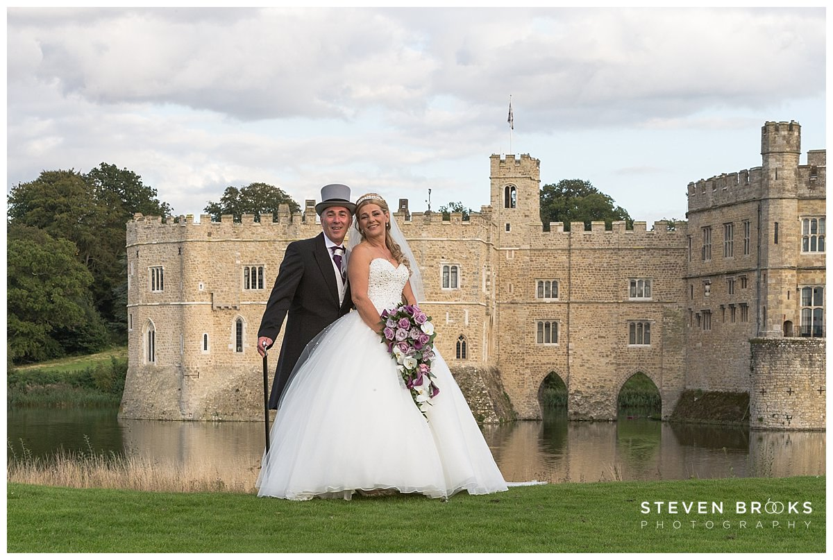 Leeds Castle wedding photographer steven brooks photographs the bride and groom in the grounds by the moat of Leeds Castle