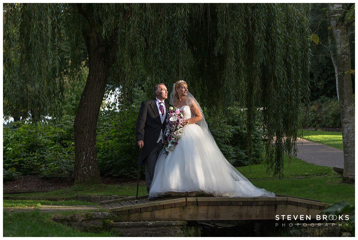 Leeds Castle wedding photographer steven brooks photographs the bride and groomon small bridge over stream at Leeds Castle