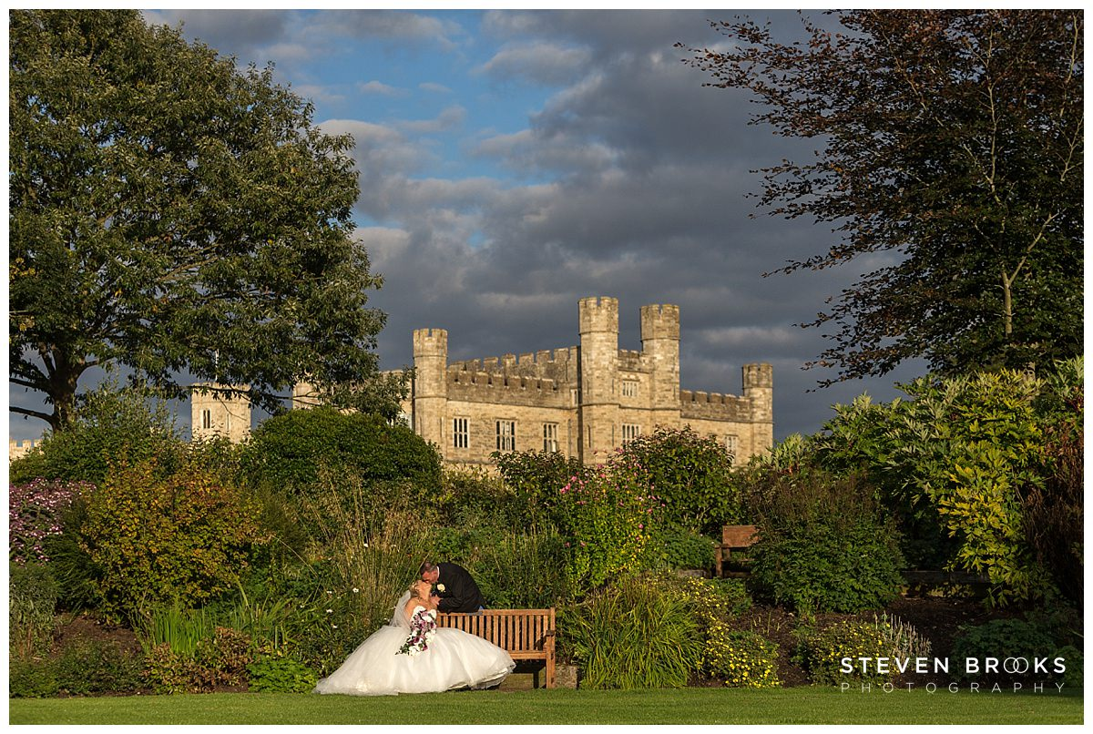 Leeds Castle wedding photographer steven brooks photographs the bride and groom kissing in the grounds with Leeds Castle in the background