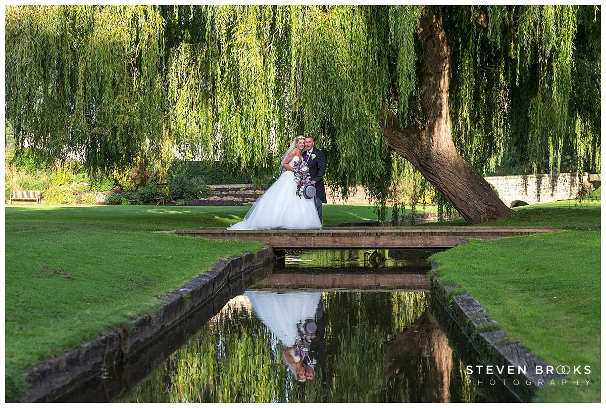 Leeds Castle wedding photographer steven brooks photographs the bride and groom on a small bridge at Leeds Castle with reflection in the stream