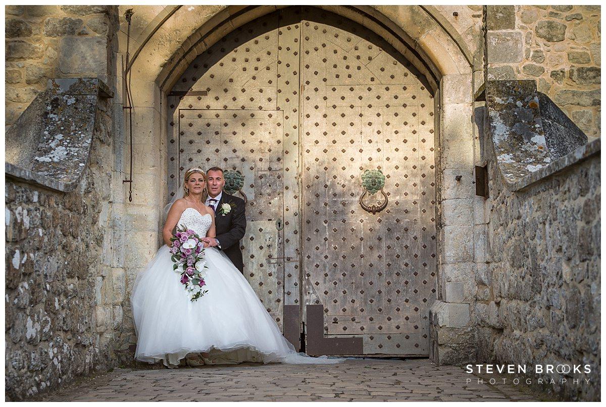 Leeds Castle wedding photographer steven brooks photographs the bride and groom by the main entrance of Leeds Castle