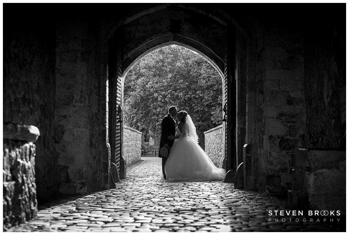 Leeds Castle wedding photographer steven brooks photographs the bride and groom in the archway at Leeds Castle