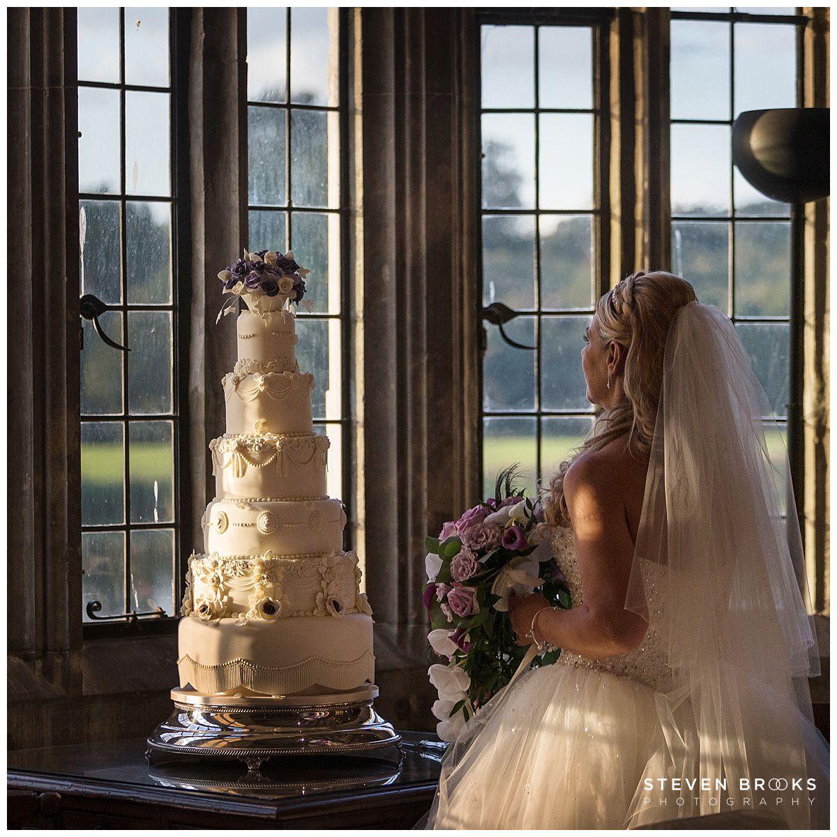 Leeds Castle wedding photographer steven brooks photographs the bride admiring the wedding cake at Leeds Castle