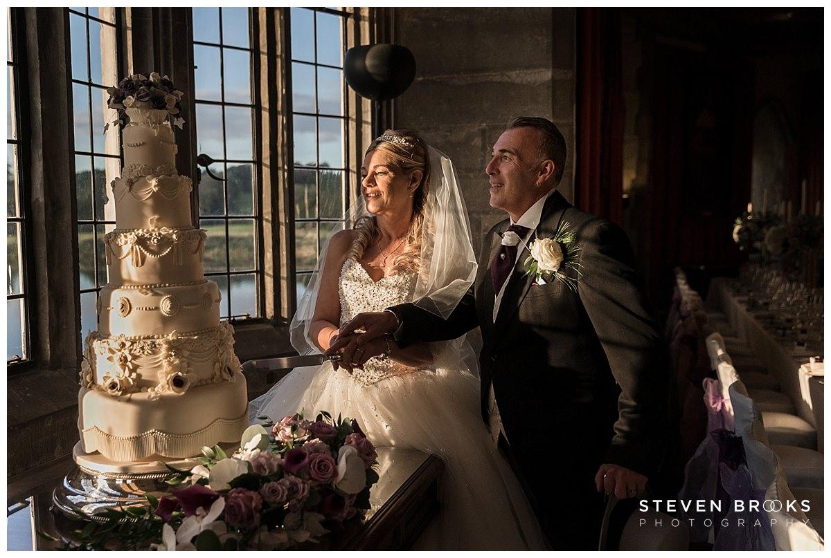 Leeds Castle wedding photographer steven brooks photographs the bride and groom cutting the wedding cake at Leeds Castle in the banqueting room