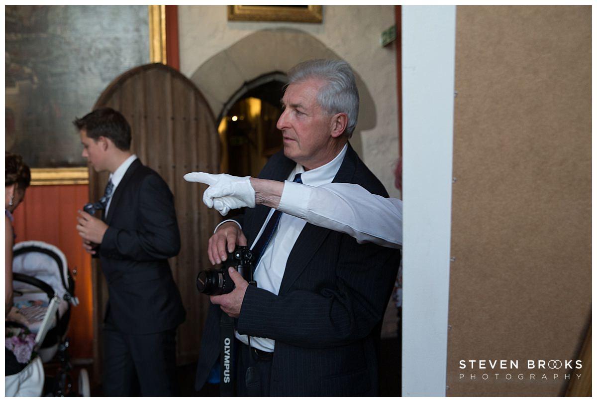 Leeds Castle wedding photographer steven brooks photographs leeds castle staff directing guest at Leeds Castle