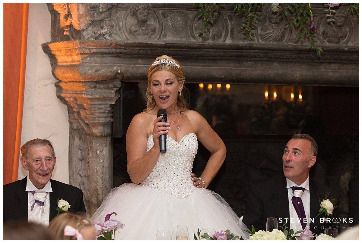 Leeds Castle wedding photographer steven brooks photographs the bride during the wedding breakfast making her speech at Leeds Castle