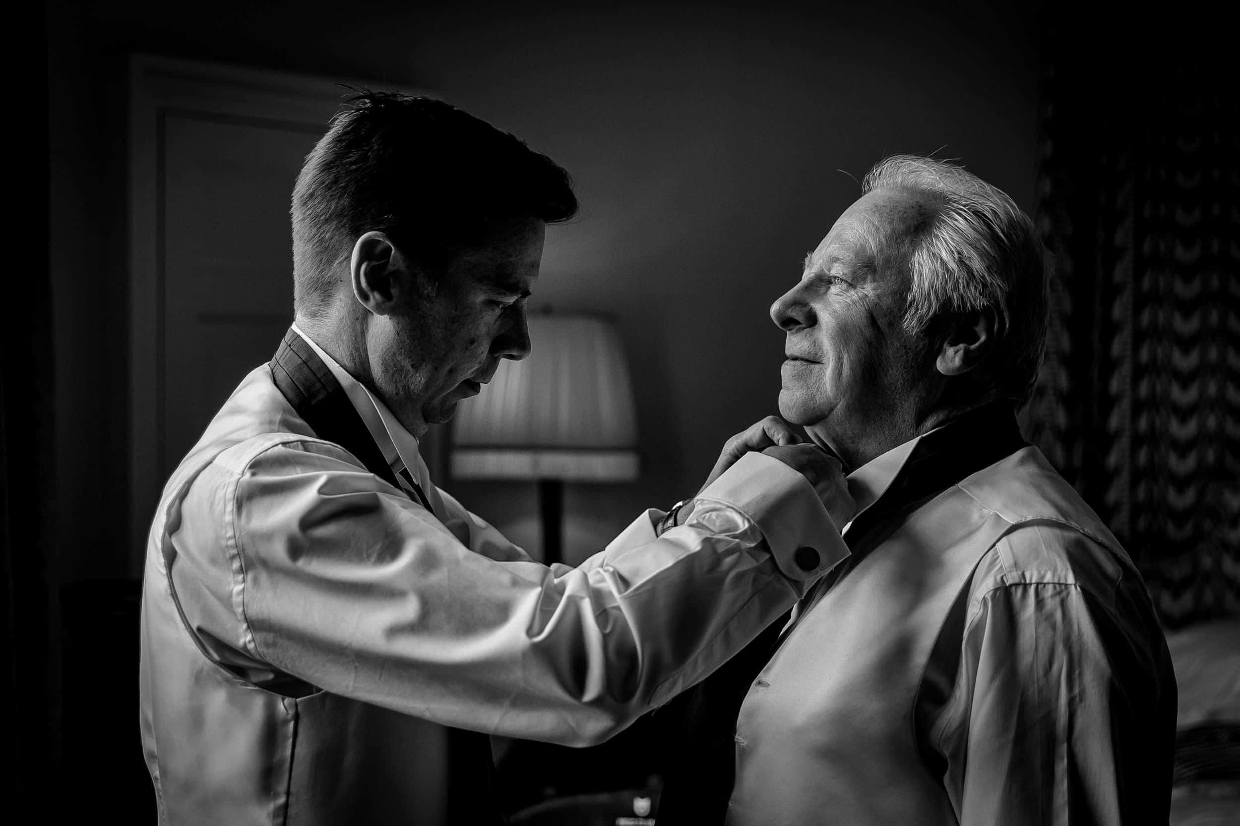 father of the groom having his tie adjusted photographed by steven brooks wedding photographer