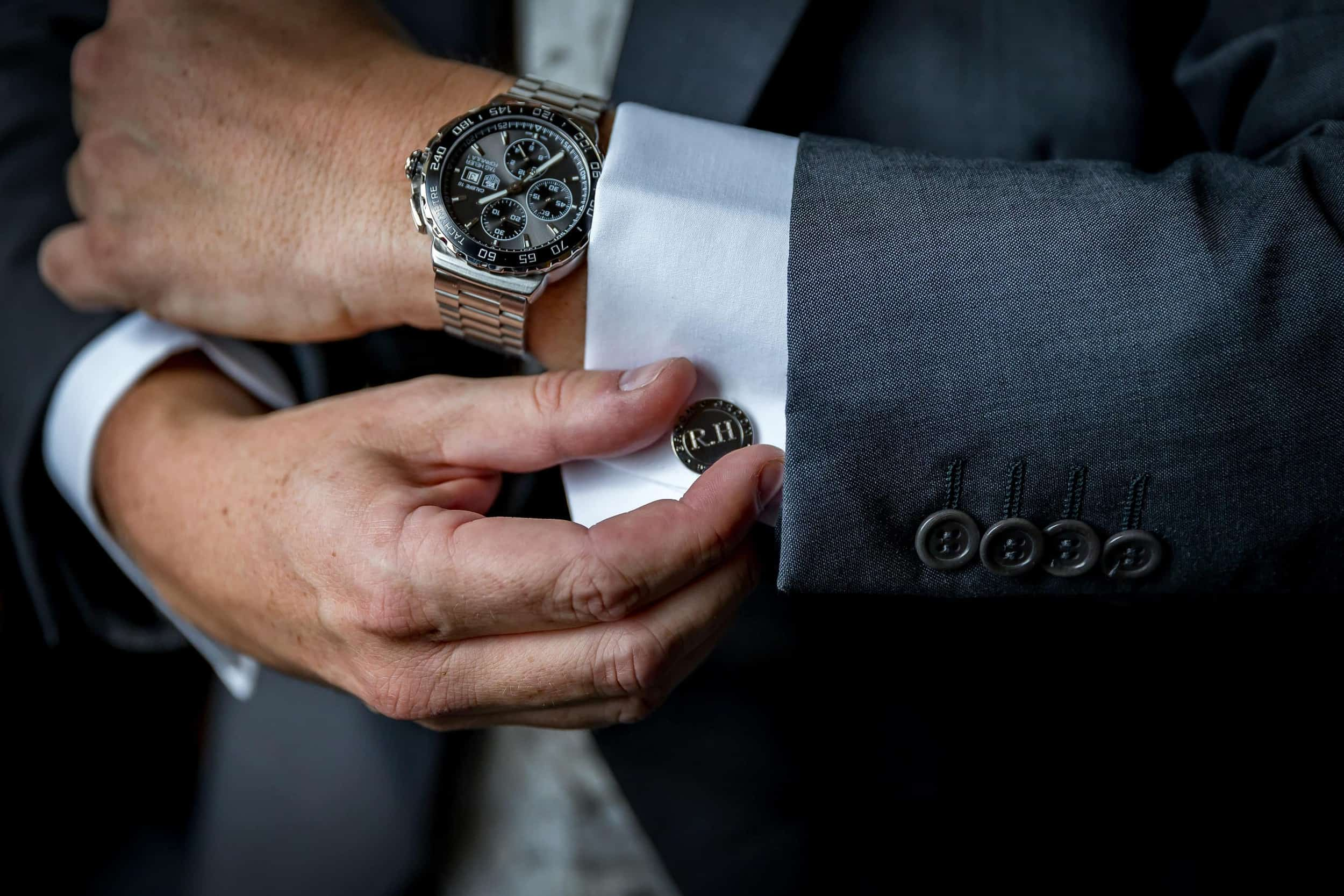 groom adjusting his cuff links before his wedding