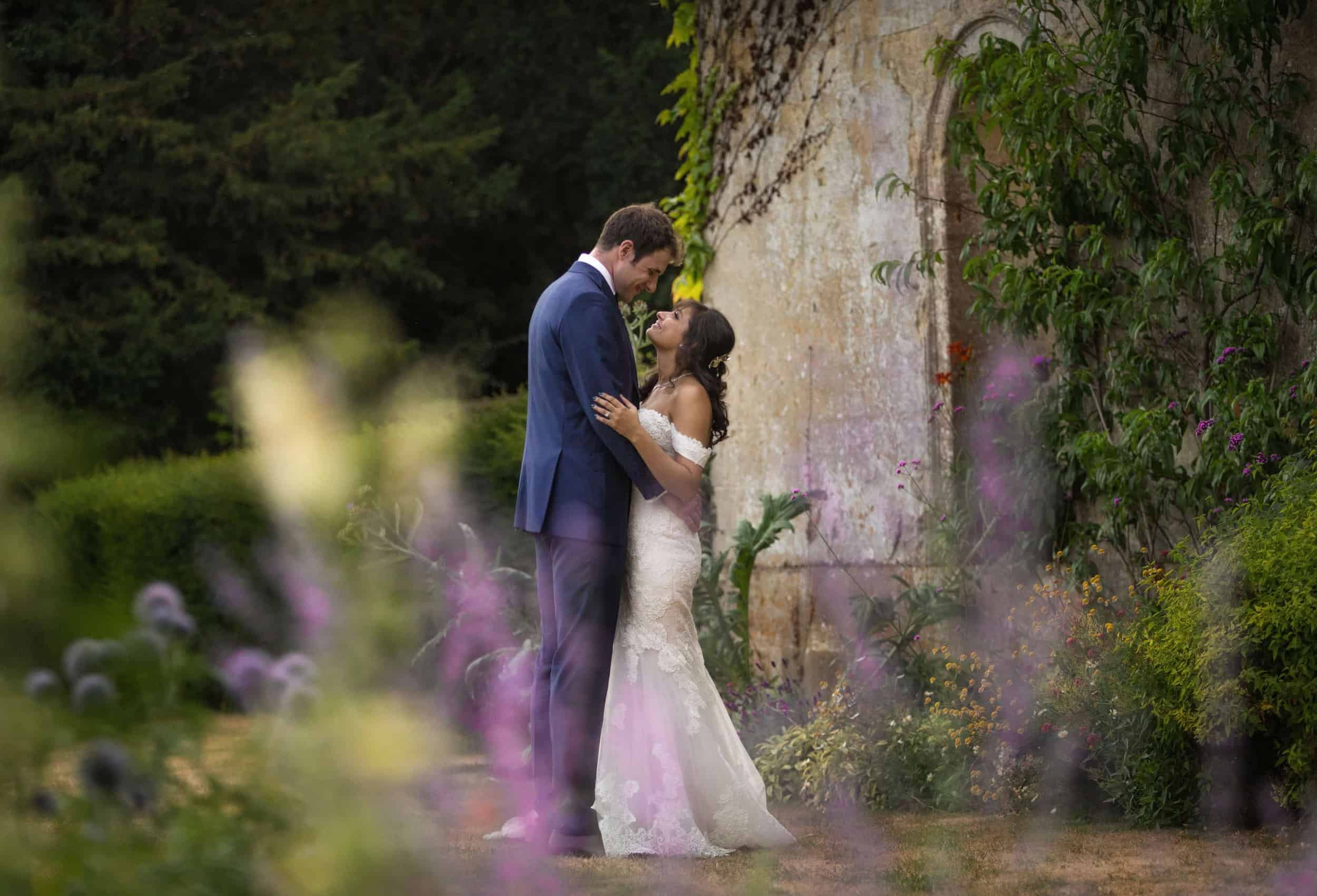 bride and groom in an embrace in the gardens of kirtlington park.