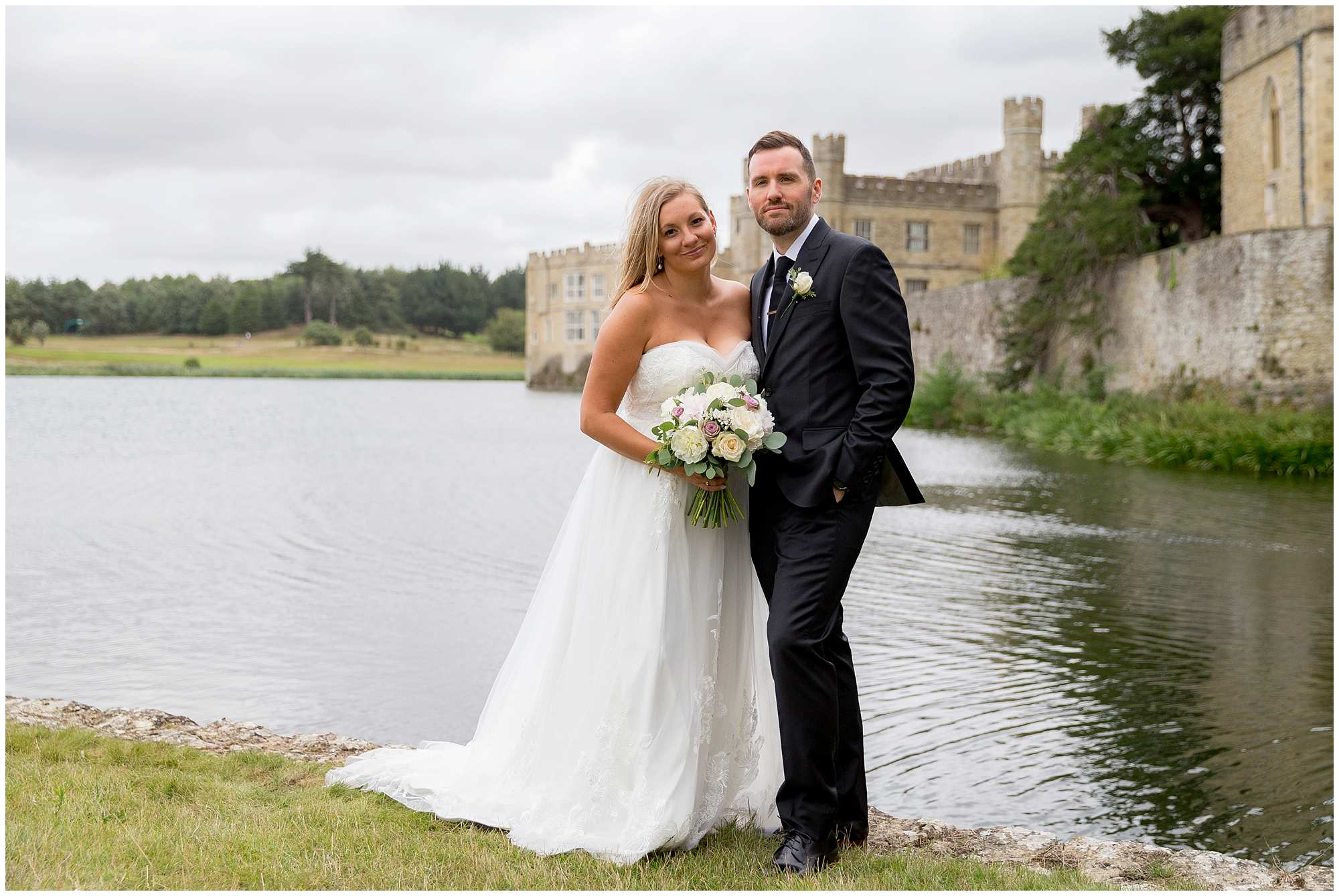 bride and groom together with leeds castle in the background